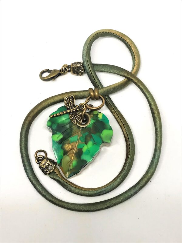 Ivy leaf dappled green created with recycled material. Hung with a charm on a hand dyed silk cord.
