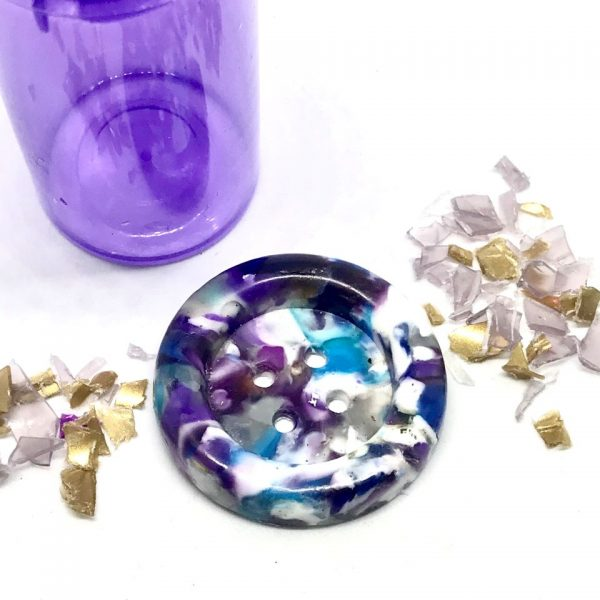 large purple white button with shreds